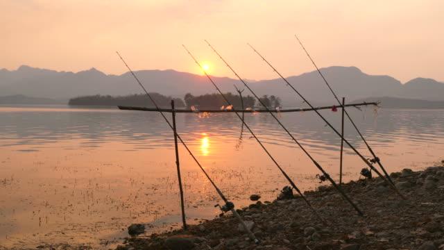美しい日の出で静かな湖の横に釣り竿 ビデオ