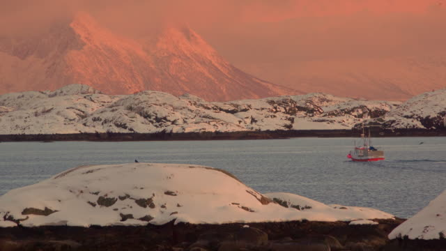 vídeos de stock e filmes b-roll de fishing ship at sunset in norwegian fjord - lofoten