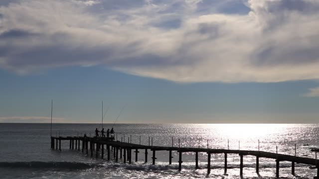 vídeos de stock e filmes b-roll de fishmans on empty pier catching fish. sunlight reflection in coming waves seascape. - fishman