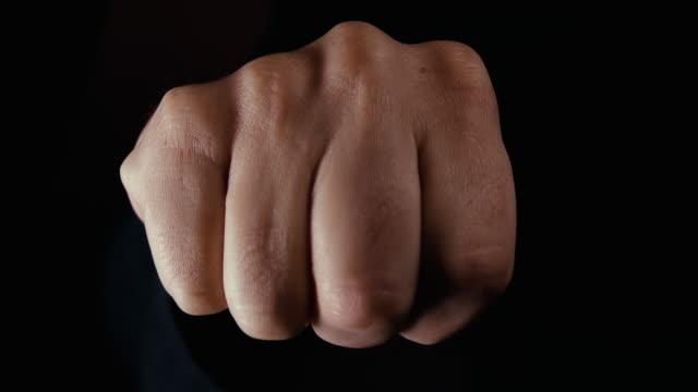 fist appearing in an aggressive manor close to camera - colpire con un pugno video stock e b–roll