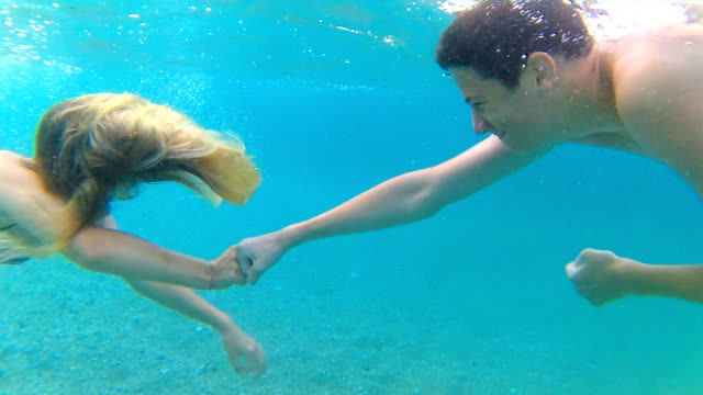Fist bump underwater Brother and sister performing fist bump while diving in the sea, handheld shot cousin stock videos & royalty-free footage