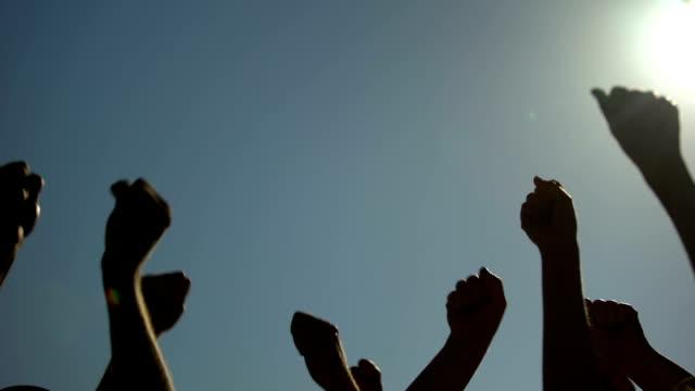 pugni di persone sollevate in aria, che protestano e colpiscono per i diritti umani - pugno video stock e b–roll