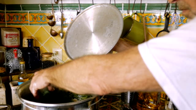 A fit active senior puts sprigs of herbs in a large pot of soup in slow motion video