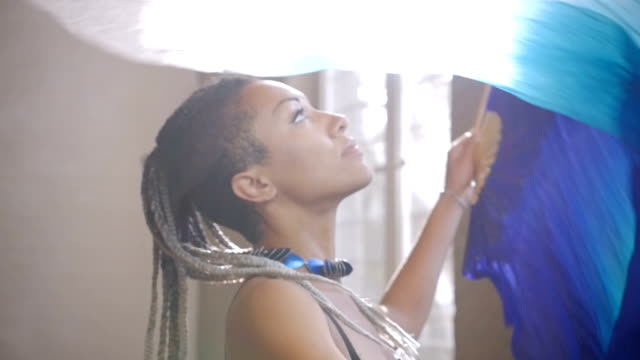 A fit African American women with braids dancing with fabric fans in sunlight video