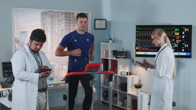 Fit athlete suddenly stops running on treadmill and interrupting stress test Fit athlete suddenly stops running on treadmill and interrupting stress test while mixed race team working on his medical record in sports lab. electrode stock videos & royalty-free footage