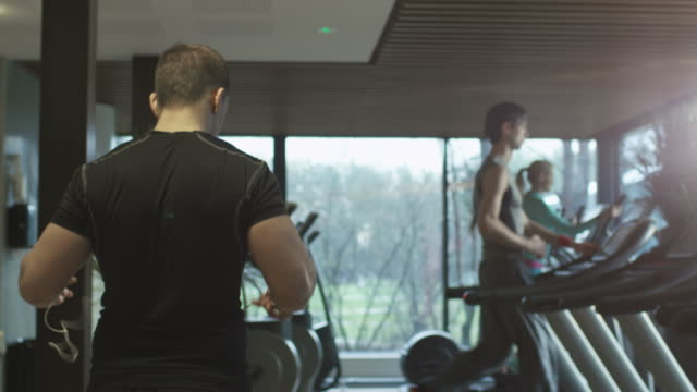 Fit athletic man is starting to run on the treadmill in the sport gym with earphones. video