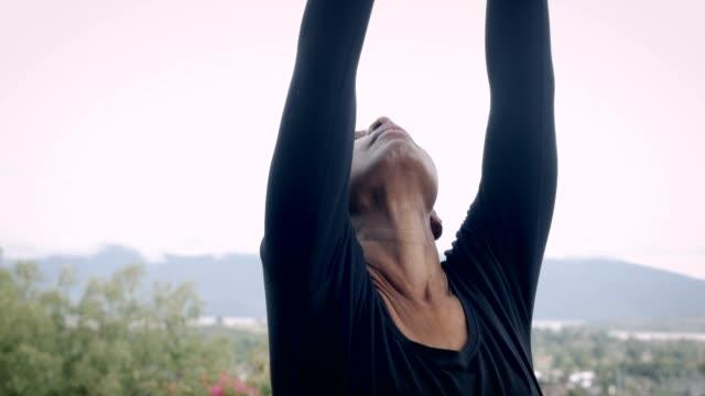 fit athletic senior woman stretching her spine outdoors with yoga - rozciągać filmów i materiałów b-roll