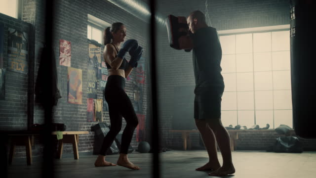 Fit Athletic Woman Kickboxer Punches the Punching Pads During a Workout in Gym. She's Beautiful and Energetic. Strong Trainer is Holding the Boxing Pads. Intense Self-Defence Training.