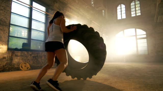 fit athletic woman lifts tire as part of her cross fitness/ bodybuilding training. - irriducibilità video stock e b–roll