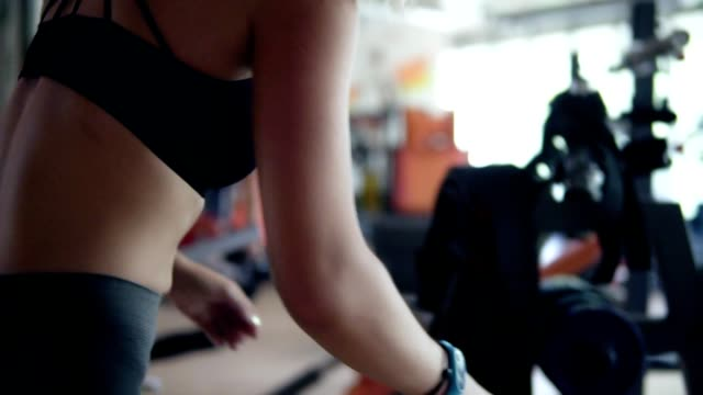 Fit blonde girl in gym putting weights wheel on a bar for exercising. Preparing for training at gym