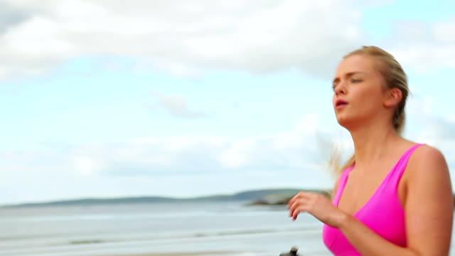 fit блондинка бег на пляже - спортивный бюстгальтер стоковые видео и кадры b-roll