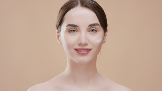 Fit Caucasian girl applies face cream on her cheek smiling wide Fit attractive Caucasian girl with brown hair in ponytail and bare shoulders applies face cream on her cheek smiling wide against beige ripple background | Face cream commercial lip balm stock videos & royalty-free footage