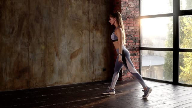 vídeos de stock e filmes b-roll de fit caucasian girl doing stretching exercises legs indoor. girl doing lunges stretching. fit fitness sports model exercising for glute muscles in gym. slow motion footage - agachar se