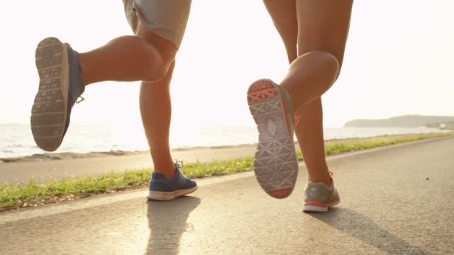 stockvideo's en b-roll-footage met lage hoek zon flare paar op ontspannen fit jog met een prachtig uitzicht op de zonnige kust - running shoes
