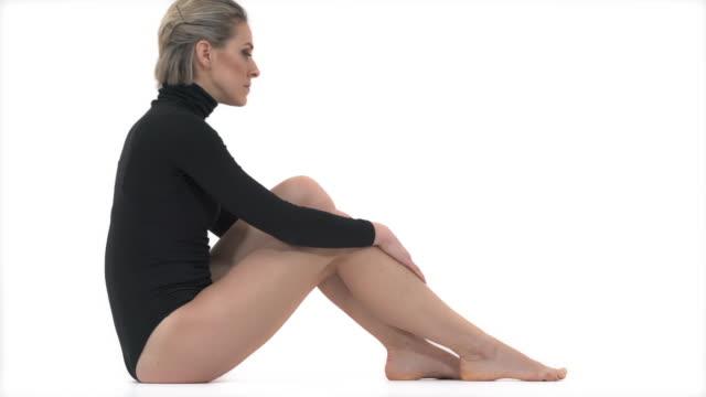 passar kvinnlig modell i svarta sportkläder avkopplande. fullängdsporträtt av sexig tjej med vältränad kropp i snygga sportkläder som sitter i studion - gympingdräkt bildbanksvideor och videomaterial från bakom kulisserna