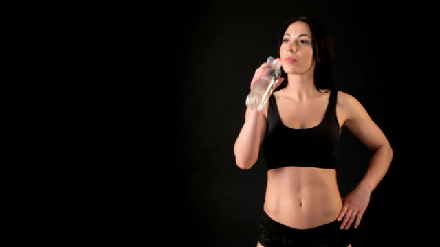 Fit girl drinks water from the bottle video