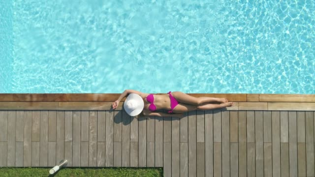 aerial cinemagraph: fit girl puts a hat over her face while suntanning by pool. - bikini video stock e b–roll