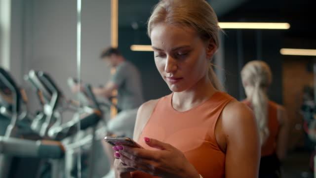 stockvideo's en b-roll-footage met fit meisje sms'en bericht op sportschool. de vrouw van de sport die mobiele telefoon in sportclub gebruikt - call center