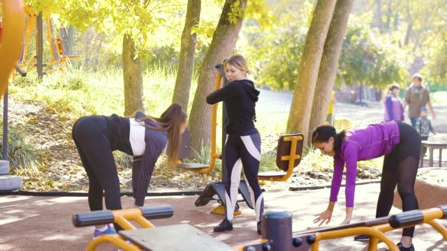 Fit girls stretching on sports ground on warm autumn day video