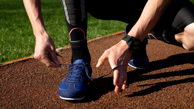 Fit jogger tying both shoelaces before running practice on track race video