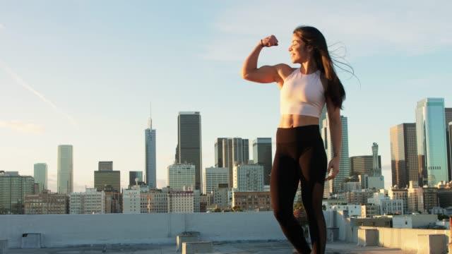 fit latina woman flexing bicep - napinać mięśnie filmów i materiałów b-roll