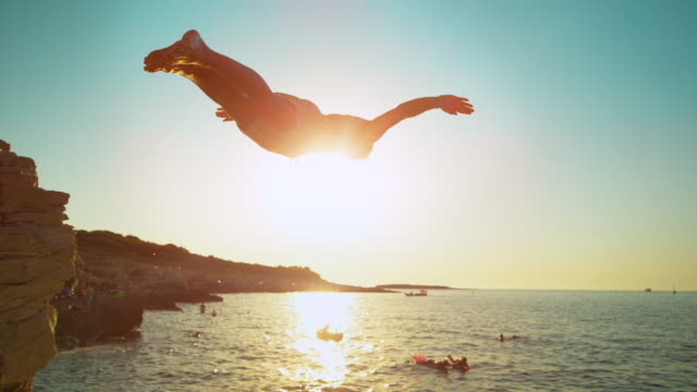 鏡頭flare:適合男性遊客潛入清涼的海水在日落。 - 懸崖 個影片檔及 b 捲影像