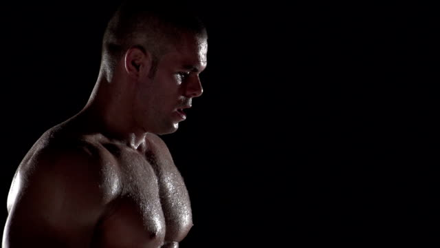 Fit man catching his breath after a workout, black background video