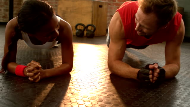 Fit man going plank exercises with trainer video