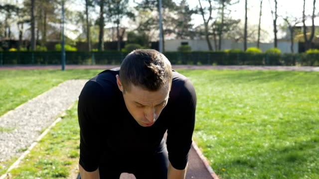 Fit man jogger stopping for break and catching breath to check race time on smartwatch then starting to running in a park video