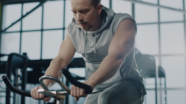 Fit man on stationary bike in gym Muscular man doing indoor cycling during a gym workout. Male athlete on stationary bike in gym. exercise bike stock videos & royalty-free footage
