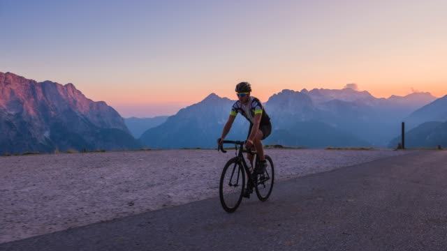 fit man road cycling in mountains at twilight - ciclismo su strada video stock e b–roll