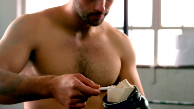 Fit man scooping protein powder video