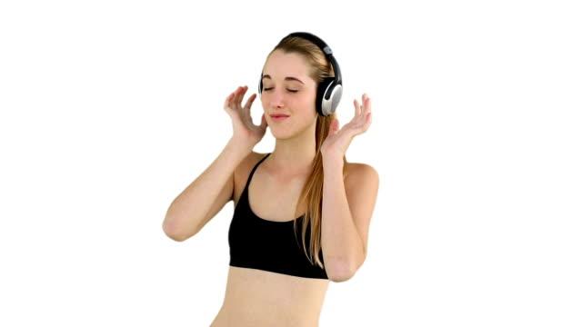 dopasowanie model słuchanie muzyki i uśmiechania się, - biustonosz sportowy filmów i materiałów b-roll