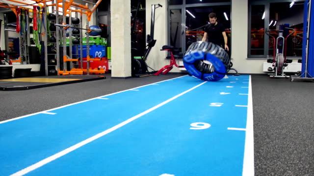 stockvideo's en b-roll-footage met fit gespierde man doen sportschool oefeningen uitwerkend opheffing van een grote rubberen band in een sportschool, lage hoekmening in een gezonde levensstijl en fitness concept, zijaanzicht - bankdruktoestel