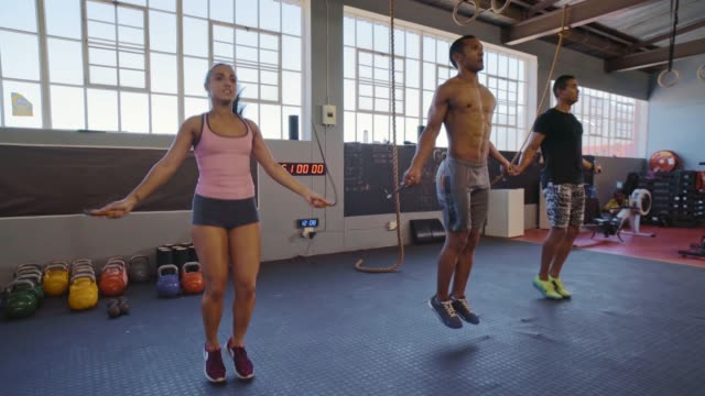 Fit muscular people skipping rope Athletic woman and men skipping rope in industrial style gym cross training stock videos & royalty-free footage