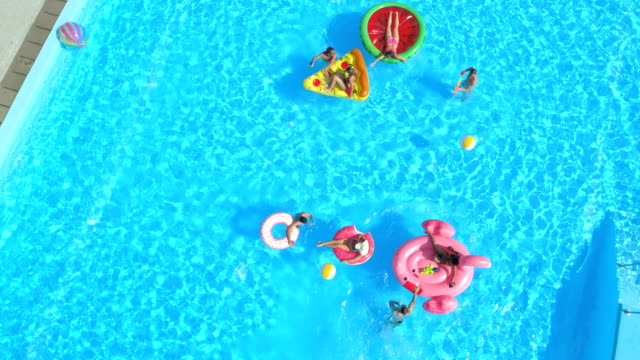 vídeos de stock e filmes b-roll de aerial top down: fit people in pool having water fight on fun inflatable floats - brinquedos na piscina