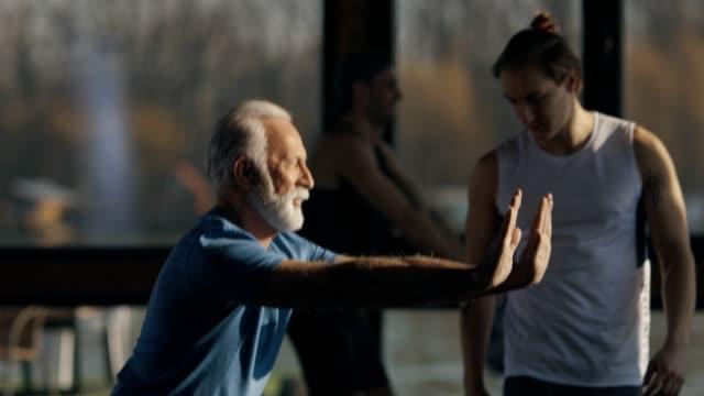 vídeos de stock e filmes b-roll de fit senior man at the gym - agachar se