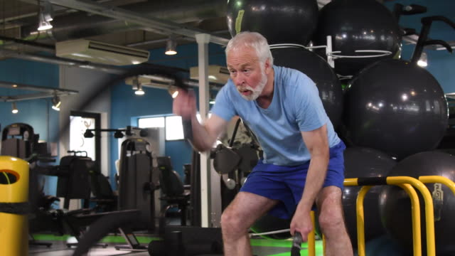 Fit senior man using ropes to workout at gym video