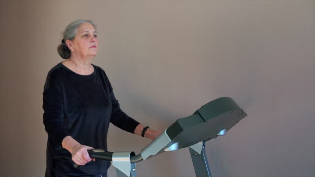 fit senior woman at home on treadmill doing cardio work out. - runner rehab gym video stock e b–roll
