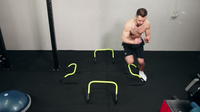 Fit shirtless man jumping over obstacles in a gym video