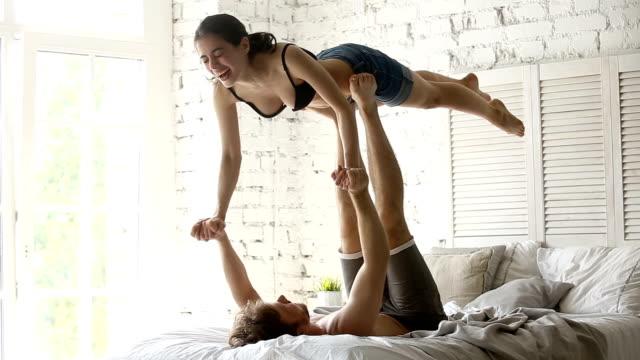 vídeos y material grabado en eventos de stock de ajuste deportivo joven pareja practicando yoga acro juntos en la cama - tablón