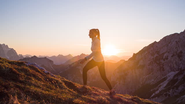 Fit woman athlete maintaining a healthy lifestyle, hiking in mountains over rocky trails and grassy slopes at sunset
