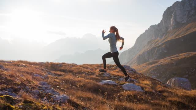 fit-sportlerin, die einen gesunden lebensstil pflegt, in den bergen über felsige wanderwege und grasbewachsene hänge bei sonnenuntergang läuft - hell beleuchtet stock-videos und b-roll-filmmaterial