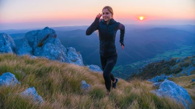 fit kvinna idrottare idrotts träning i bergen, kör uppför över steniga stigar och gräs bevuxna sluttningar - jogging hill bildbanksvideor och videomaterial från bakom kulisserna