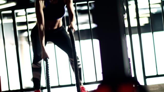 Fit woman battling ropes in the gym