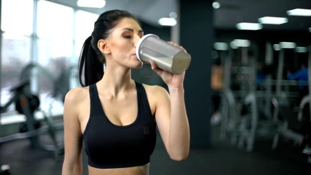 vídeos de stock, filmes e b-roll de apta mulher bebendo batido de proteínas após o treino, nutrição de ganho muscular, saúde - medicina esportiva