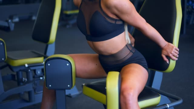 Fit woman exercising at hip abductor machine video
