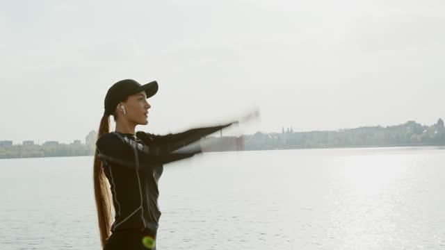 donna in forma che si allena vicino al fiume in città - berretto video stock e b–roll