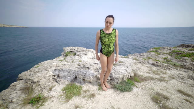 Fit woman in gymnastics leotard on a cliff above the sea. Pole dance fitness Fit woman in gymnastics leotard on a cliff above the sea. Pole dance fitness workout outdoors. Steadicam shot leotard stock videos & royalty-free footage