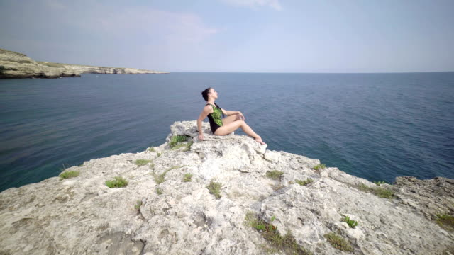 Fit woman in gymnastics leotard  posing on the edge of rock above the sea Fit woman in gymnastics leotard  posing on the edge of rock above the sea. Pole dance fitness workout outdoors. Steadicam shot leotard stock videos & royalty-free footage